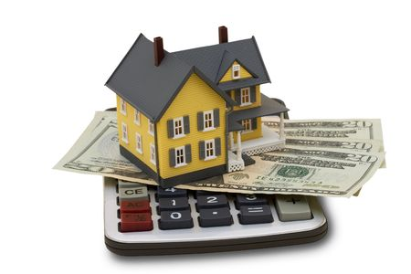 A model house sitting with a calculator and twenty dollar bills on a white background with clipping path, mortgage calculator photo