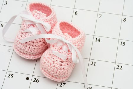 due: Pink baby booties on a calendar background, baby due date