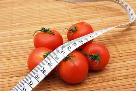 Five ripe tomatoes with measuring tape sitting on a  wooden background, weight loss Stock Photo