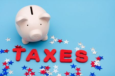 spending: A piggy bank with the word taxes and stars on a blue background, Saving Money on Taxes Stock Photo