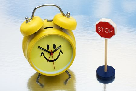wrong way sign: A yellow retro smiley face clock sitting next to a red wrong way sign, stopping time