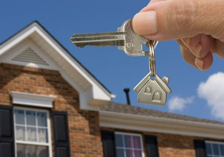 A key on a house keychain in a person�s hand on a house and sky background, unlocking your door photo