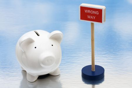 wrong way sign: Piggy bank sitting next to a red wrong way sign, risky investments Stock Photo