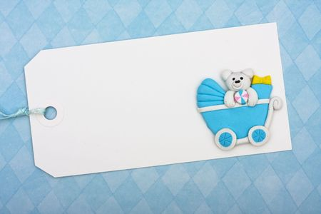 tag: A blank gift tag sitting on blue background, baby shower present