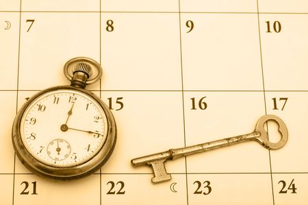 A pocket watch and a key on a calendar background, time management photo