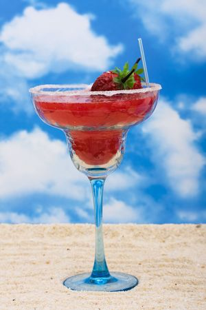 slushy: A tropical drink sitting on sand with a sky background, tropical drinks  Stock Photo