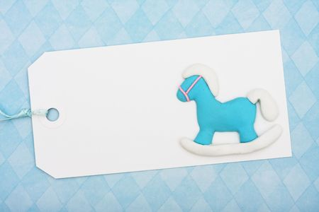 A blank gift tag sitting on blue background, baby shower present