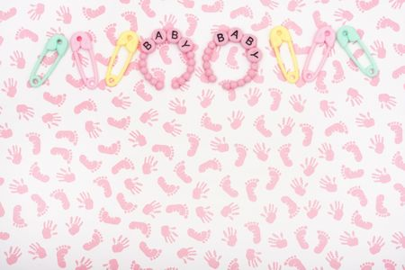due date: A pink baby pacifier with diaper pins on a calendar background, baby due date Stock Photo