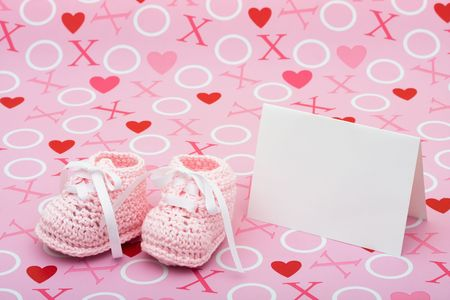 A white  card with baby booties on a pink love background, baby shower message photo
