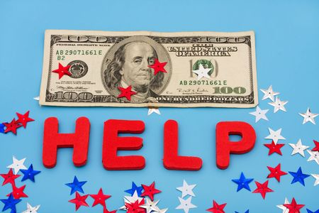One hundred dollar bill with multi coloured stars and the word help on blue background, financial help photo