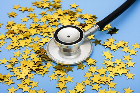 A pile of gold stars and stethoscope on a blue background, excellent healthcare Stock Photo