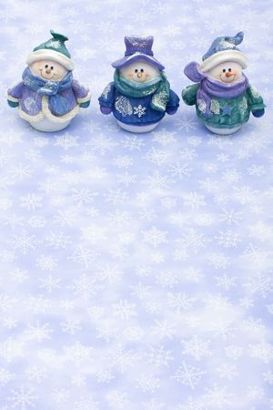Three snowman sitting together on a snowflake background, happy holidays Stock Photo - 5479477