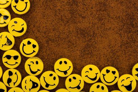 茶色のテクスチャ背景に黄色のスマイリー顔の多くの幸せな日 写真素材