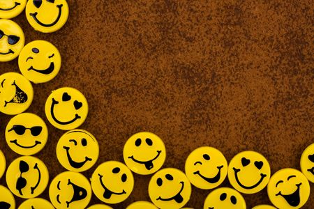 smiley: Lots of yellow smiley faces on a brown textured background, happy days Stock Photo