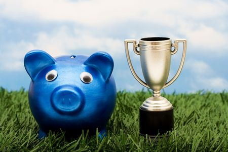 A blue piggy bank with a gold trophy sitting on grass with a sky blue background, winning with your savings photo