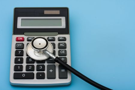 healthcare costs: A calculator and stethoscope isolated on a blue background, calculating healthcare costs