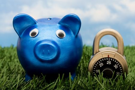 A blue piggy bank with a combination lock sitting on grass with a sky blue background, savings  photo