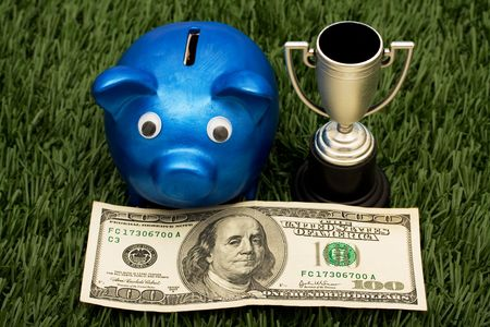 A blue piggy bank with a gold trophy sitting on grass background, winning with your savings photo