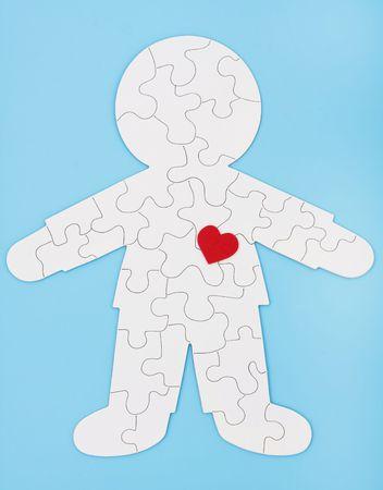 puzzelen: Een witte puzzel in de vorm van een menselijk lichaam op een blauwe achtergrond, raadselachtige lichaam Stockfoto