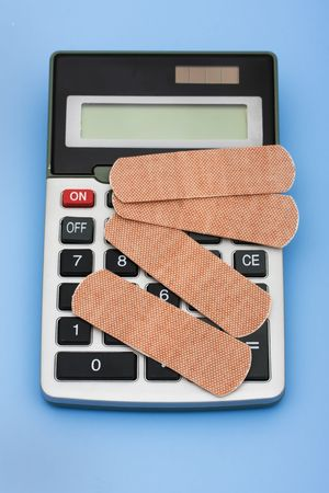 pricey: A calculator and bandages on a blue background, calculating healthcare costs Stock Photo