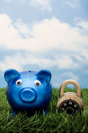 A blue piggy bank with a combination lock sitting on grass with a sky blue background, locking in your savings  photo