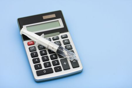 healthcare costs: A calculator and a syringe on a blue background, calculating healthcare costs