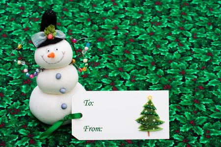 A blank gift tag with a snowman on a holly berry and leaf background, happy holidays photo