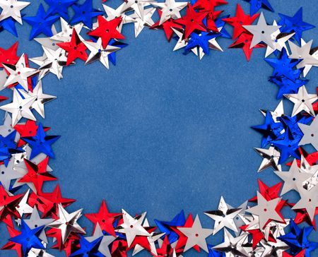 christmas in july: Close up of shiny stars making a border on a blue background, multi coloured star background