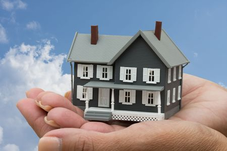 creditor: A model house sitting in hands on a sky background, mortgage help Stock Photo