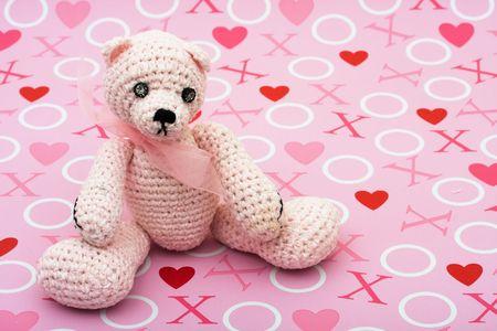 A pink handmade teddy bear on a love background, I love you bear