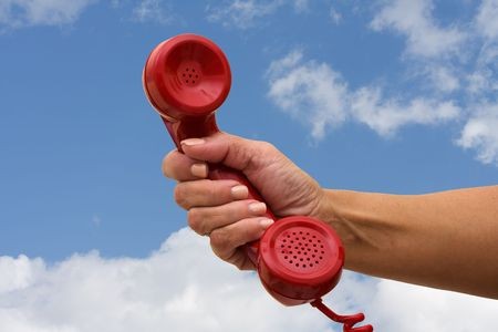 handset: A hand holding a red handset of a telephone on a sky background, answering the telephone Stock Photo