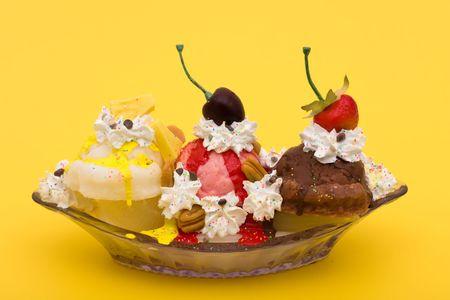 A banana split ice cream on a yellow background, ice cream sundae  photo