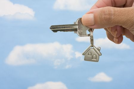 A key on a house keychain in a person�s hand isolated on a white background, unlocking your door photo