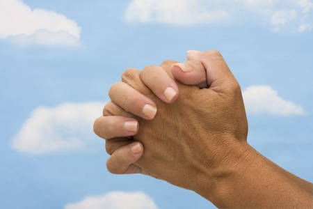 Two hands  on a sky background, praying  photo