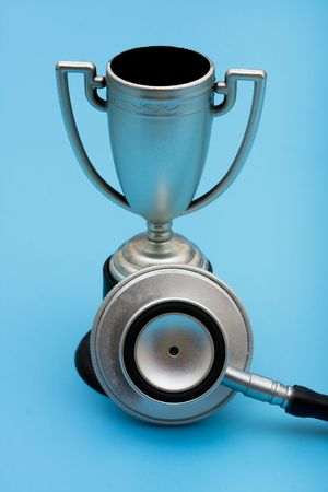 A trophy and stethoscope on a blue background, award winning healthcare services photo