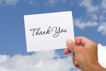 A thank you card sitting in hands on a sky background, blank card photo