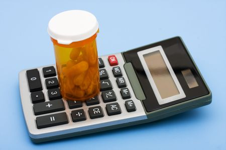 healthcare costs: A calculator and pills on a blue background, calculating healthcare costs Stock Photo