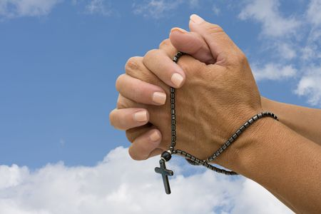 A rosary chain in a person�s hand on a sky background, praying with a rosary photo