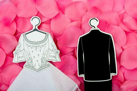 A wedding dress and tuxedo on a flower petal background, wedding dress