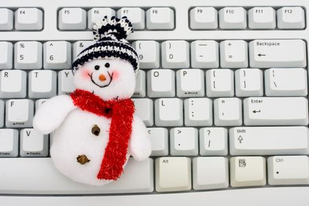 A snowman sitting on computer keyboard, Christmas shopping online photo