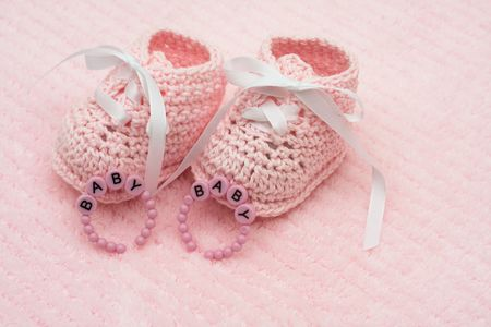 Baby booties with bracelets on a pink background, baby booties