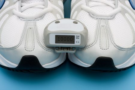 A pair of sneakers and a pedometer on a blue background, walking for a healthy heart Banco de Imagens