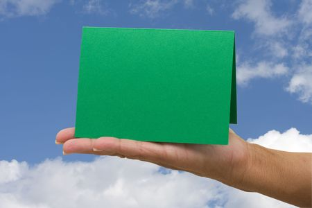 A blank card green card sitting in hands on a sky background, blank card photo