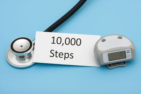 bmi: A stethoscope and a pedometer with a note on a blue background, walking for a healthy heart