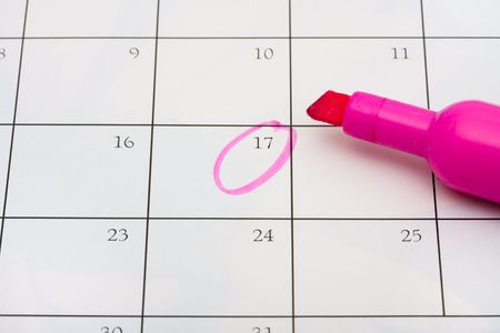 A pink highlighter with a circled day on calendar background, important date Banco de Imagens