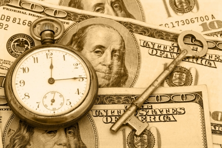 old time: A pocket watch sitting with an antique key on a hundred dollar bill background, time management Archivio Fotografico