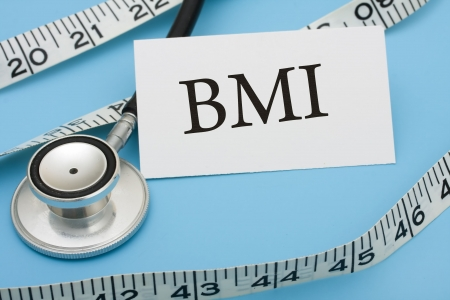 A white measuring tape and a stethoscope with a note saying BMI on a blue background, measuring health photo