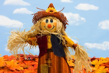 A scarecrow sitting on fall leaves on a sky background, scarecrow photo
