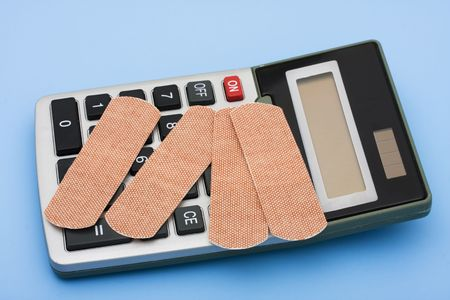 healthcare costs: A calculator and bandages on a blue background, calculating healthcare costs Stock Photo