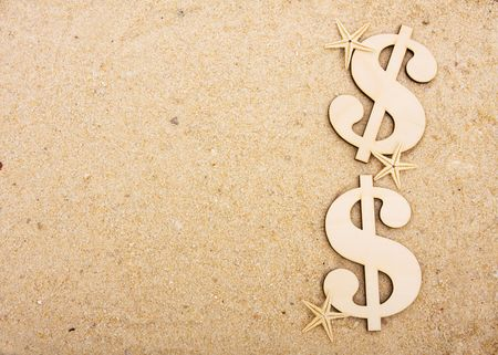 A gold coloured dollar symbol sitting on a beach with starfish, vacation money photo